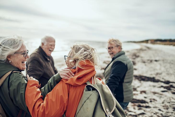 4 eldre mennesker går tur på stranden